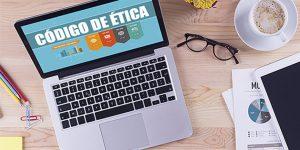 mesa de escritório com notebook com código de ética no monitor