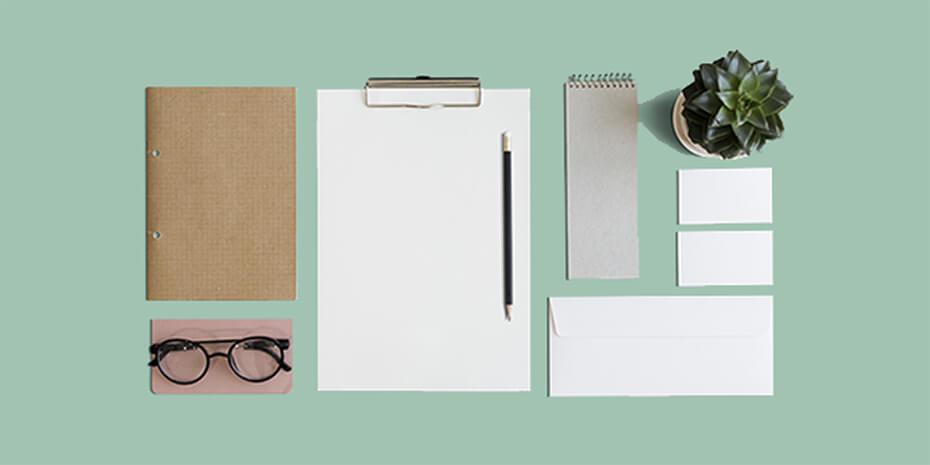 itens de papelaria corporativa que compõem identidade visual sobre a mesa