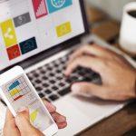 mão digitando em notebook e segurando smartphone para montar um plano de marketing digital