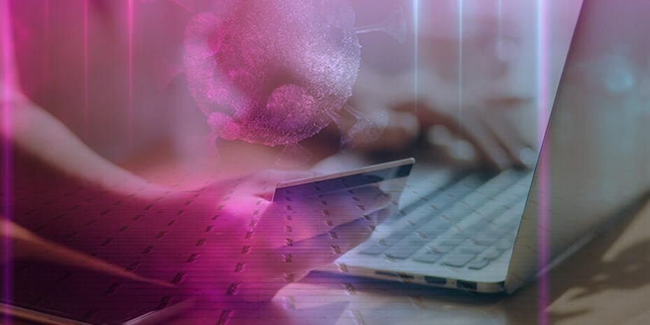 Mão segura cartão para pagamento enquanto digita no computador