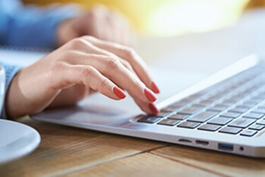 Mãos femininas digitando em notebook